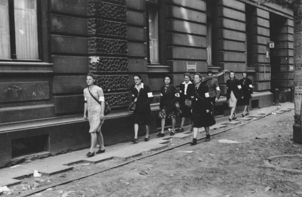 Grupa sanitariuszek z kompanii 'Koszta' przechodząca obok domu przy ulicy Moniuszki 9, fot. Eugeniusz Lokajski, Muzeum Powstania Warszawskiego
