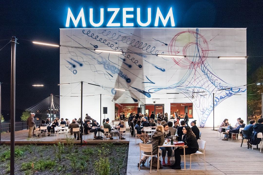 Muzeum Sztuki Nowoczesnej zzewnątrz, wieczorem, jasno rozświetlony neon MUZEUM. Ludzie siedzą irozmawiają przy stolikach